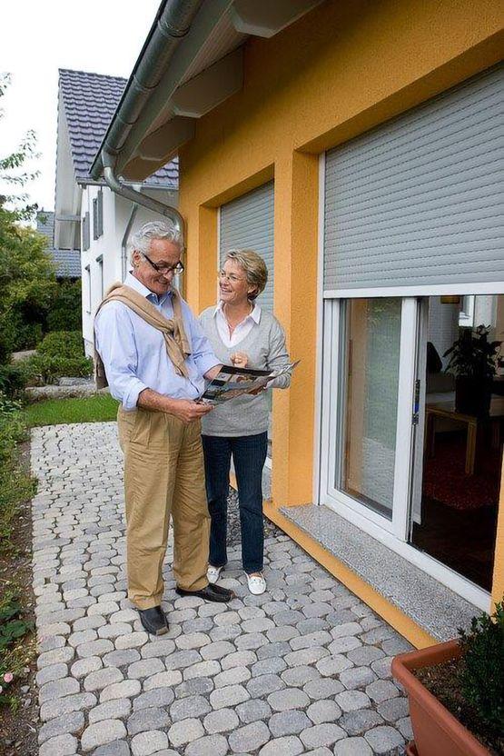 Älteres Ehepaar schaut von der Terrasse auf einen Rollladen